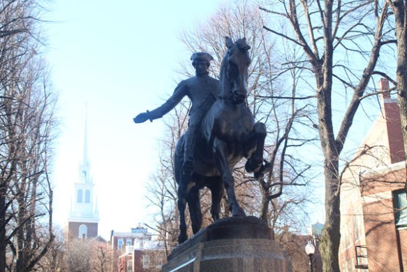 Statue commemorating Paul Revere's famous ride to warn that the British were coming. Church where the two lanterns were hung in the background.